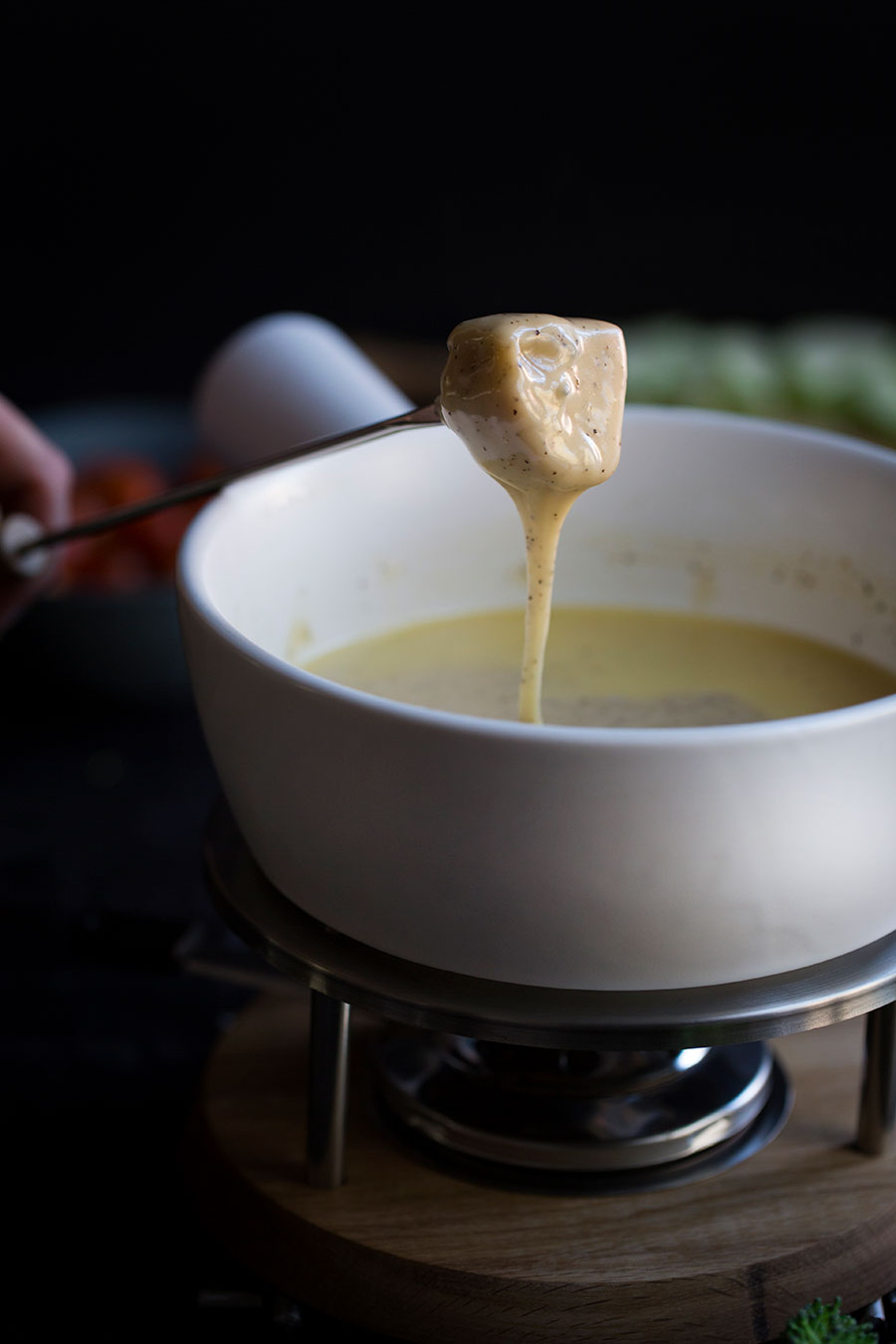 A closeup photo of gooey cheese fondue dripping off bread.