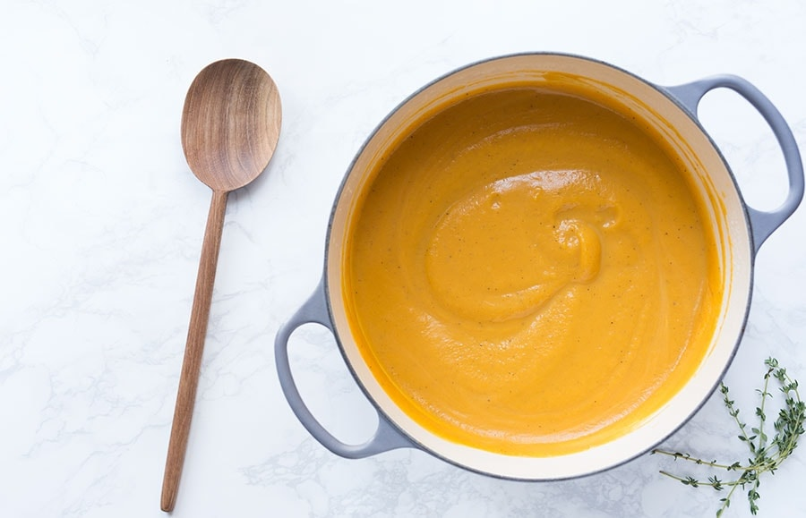 Photo shows this homemade butternut squash soup recipe from overhead, still in a saucepan.