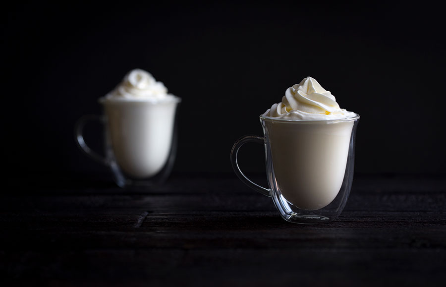 Two cups of white hot chocolate topped with whipped cream.