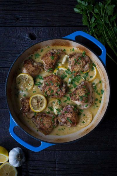 A photo of crispy baked chicken thighs in a blue casserole dish