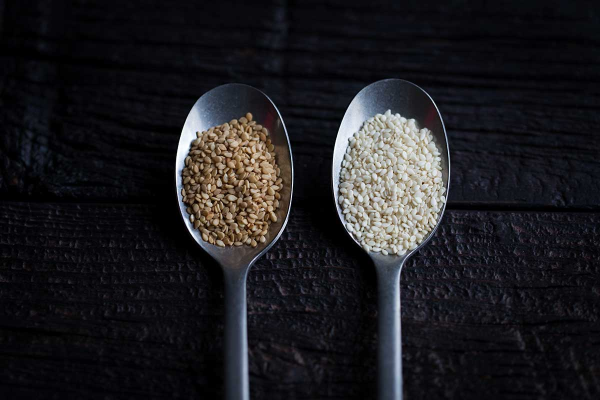 Toasted sesame seeds in a spoon next to sesame seeds that have not been toasted