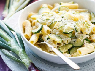 A bright photo of pasta in a bowl topped with zucchini and cheese