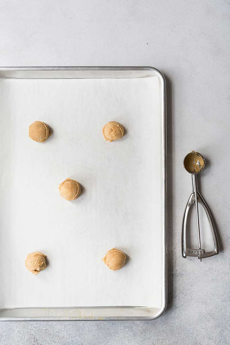 Scooped dough for the peanut butter cookie recipe on a sheet pan lined with parchment paper.
