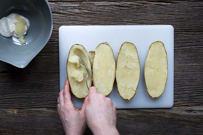 Hands scooping a the filling from a baked potato next to a large bowl with sour cream.