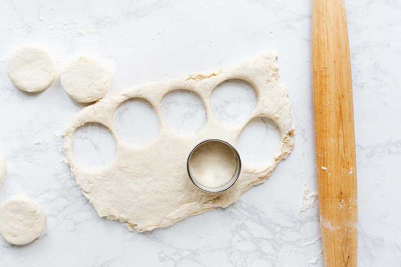 Biscuit dough rolled out with a rolling pin, then cut into with a round cutter.