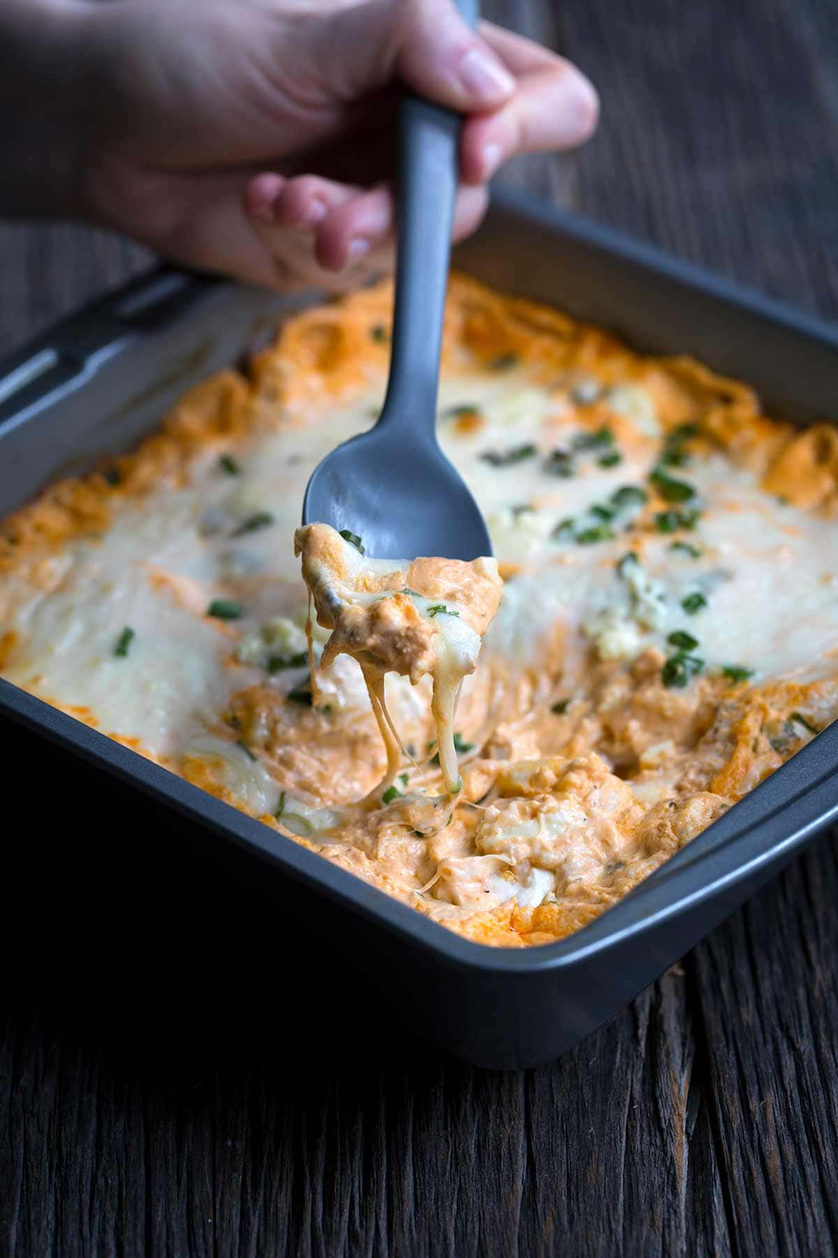 A closeup of buffalo chicken dip in a baking dish, fresh from the oven, with a lifted spoon displaying gooey cheese.
