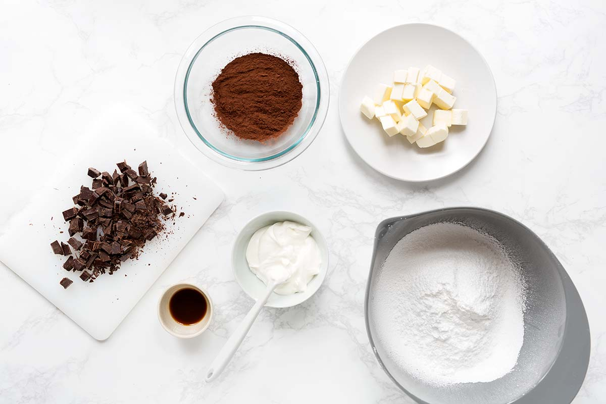 Ingredients for chocolate frosting, including powdered sugar, butter, sour cream, chocolate, cocoa powder, and vanilla.
