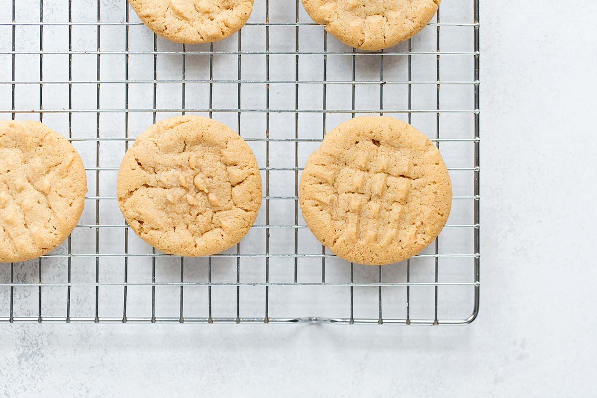 Homemade peanut butter cookies cooling on a drying rack.