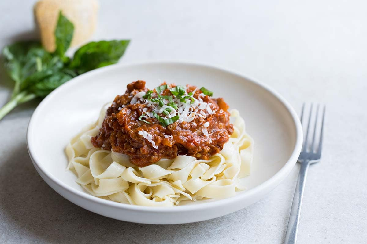 A photo of Italian meat sauce in a bowl, served over pasta and topped with cheese and basil.