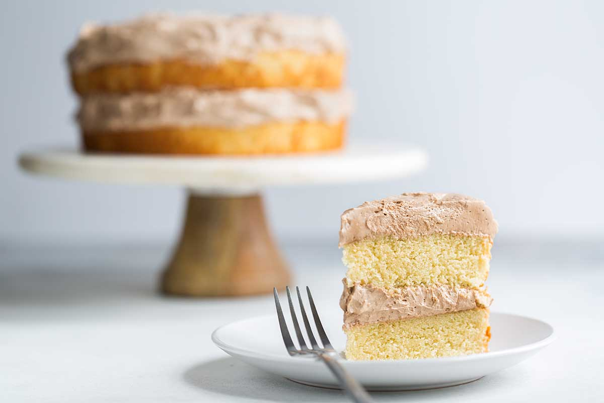 A slice of yellow cake in the foreground. A full double-layer yellow cake with chocolate buttercream is in the background.
