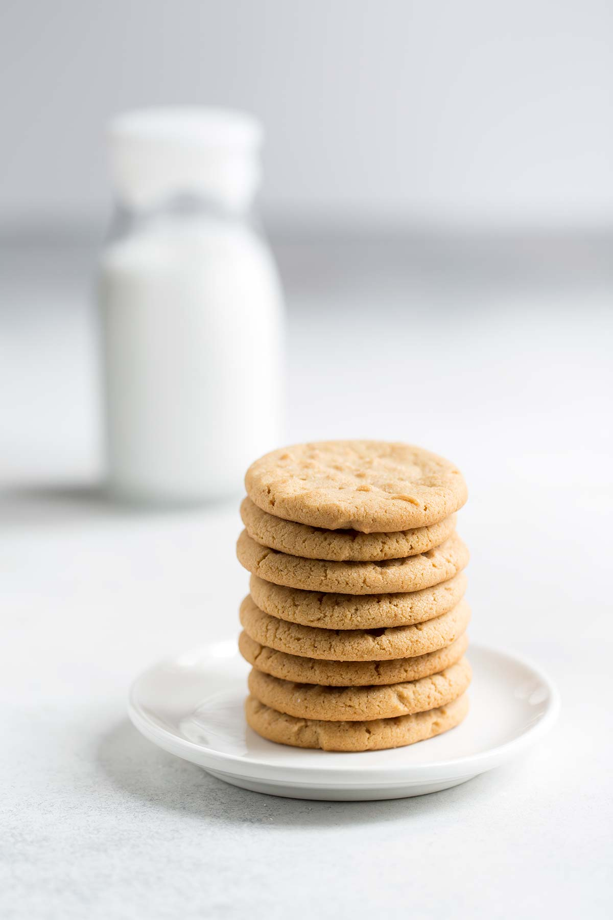 Easy peanut butter cookies stacked on a white plate in the foreground, with a glass bottle of milk in the background.