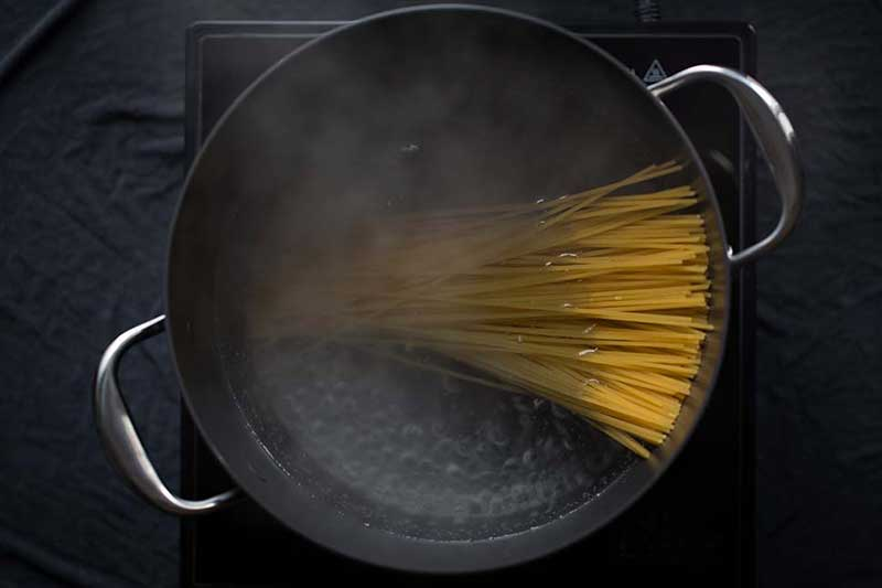 Dry pasta added to a pot of boiling water