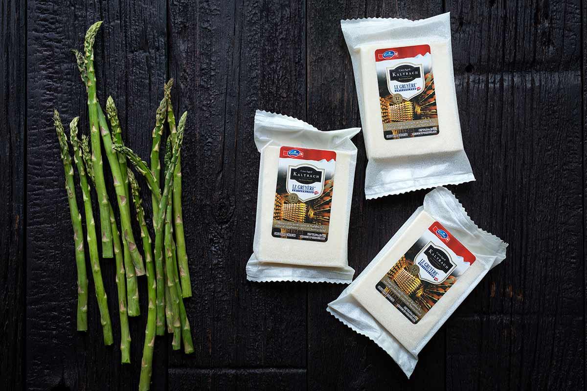 Emmi USA's Kaltbach Le Gruyére next to several stalks of fresh, seasonal asparagus.