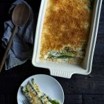 Asparagus gratin in a white casserole dish, next to one serving on a plate.