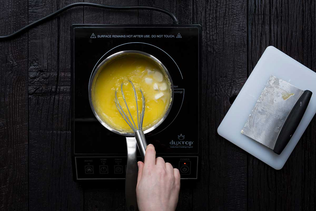 Adding butter to the lemon curd recipe.