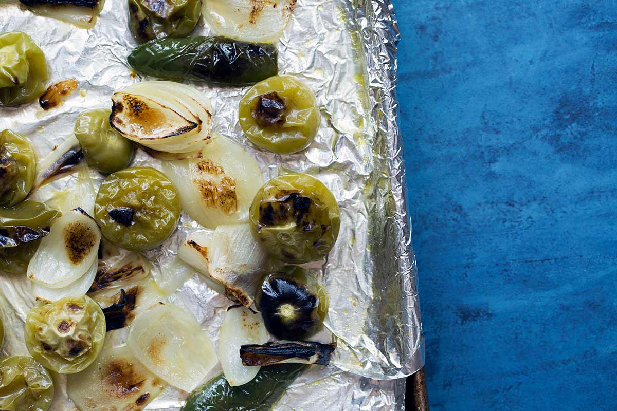 A sheet pan covered with foil, topped with broiled tomatillos, yellow onions, jalapeño peppers, and garlic.