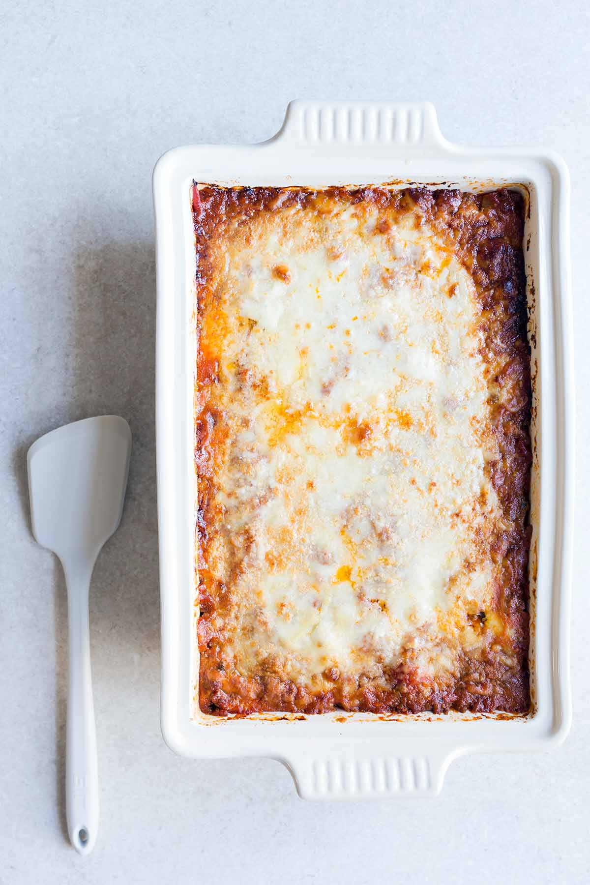 A photo of zucchini lasagna in a casserole dish on a pale backdrop.