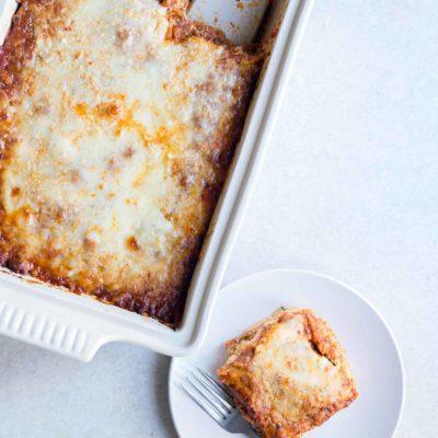 zucchini lasagna recipe in a casserole dish, next to a slice of lasagna on a plate.