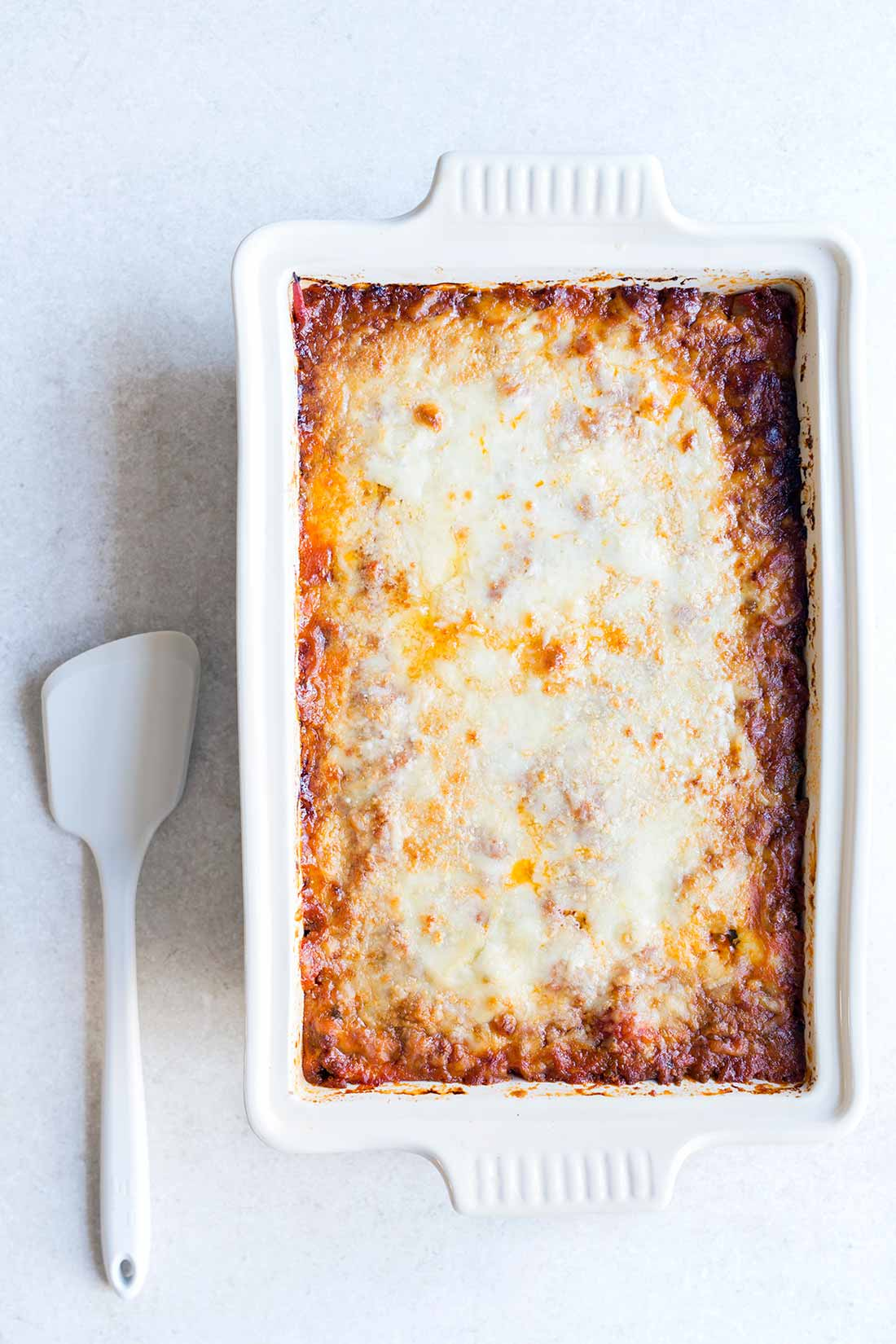 A photo of zucchini lasagna in a casserole dish on a pale backdrop.