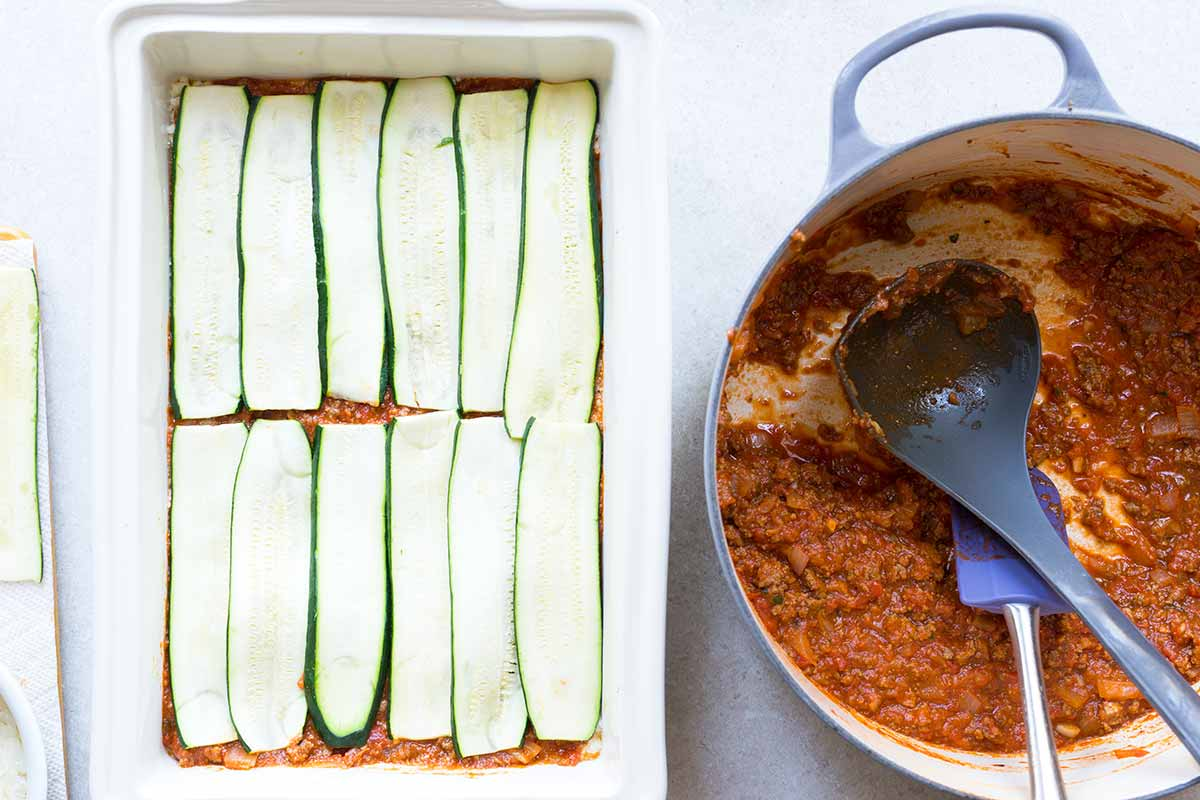 Veggie lasagna being prepared, with thin layers of zucchini spread on top of a layer of sauce.