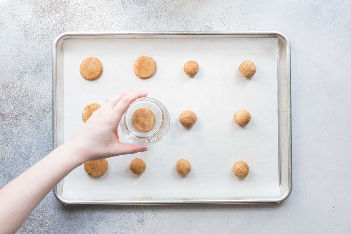 Raw snickerdoodle cookies on a sheet pan, being flattened with a drinking glass.