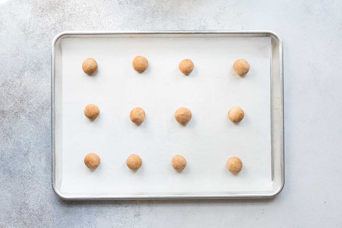 Raw snickerdoodle cookies on a sheet pan, ready to bake.