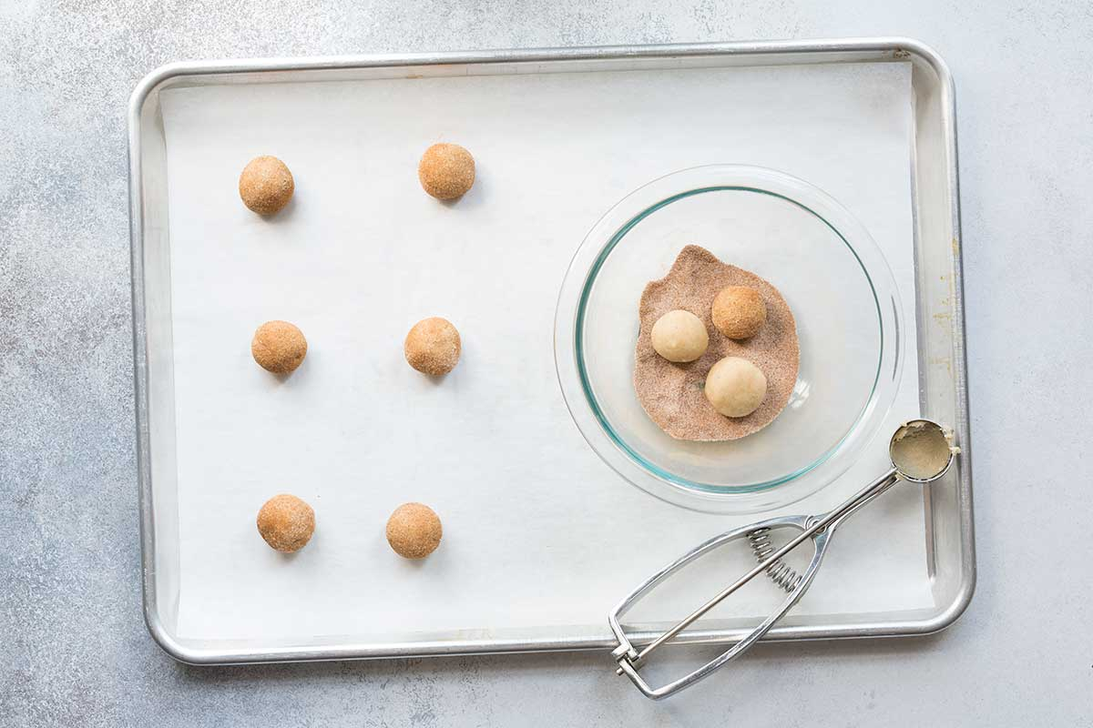 A sheet pan lined with parchment paper, topped with raw snickerdoodles next to a bowl of cinnamon-sugar mix.