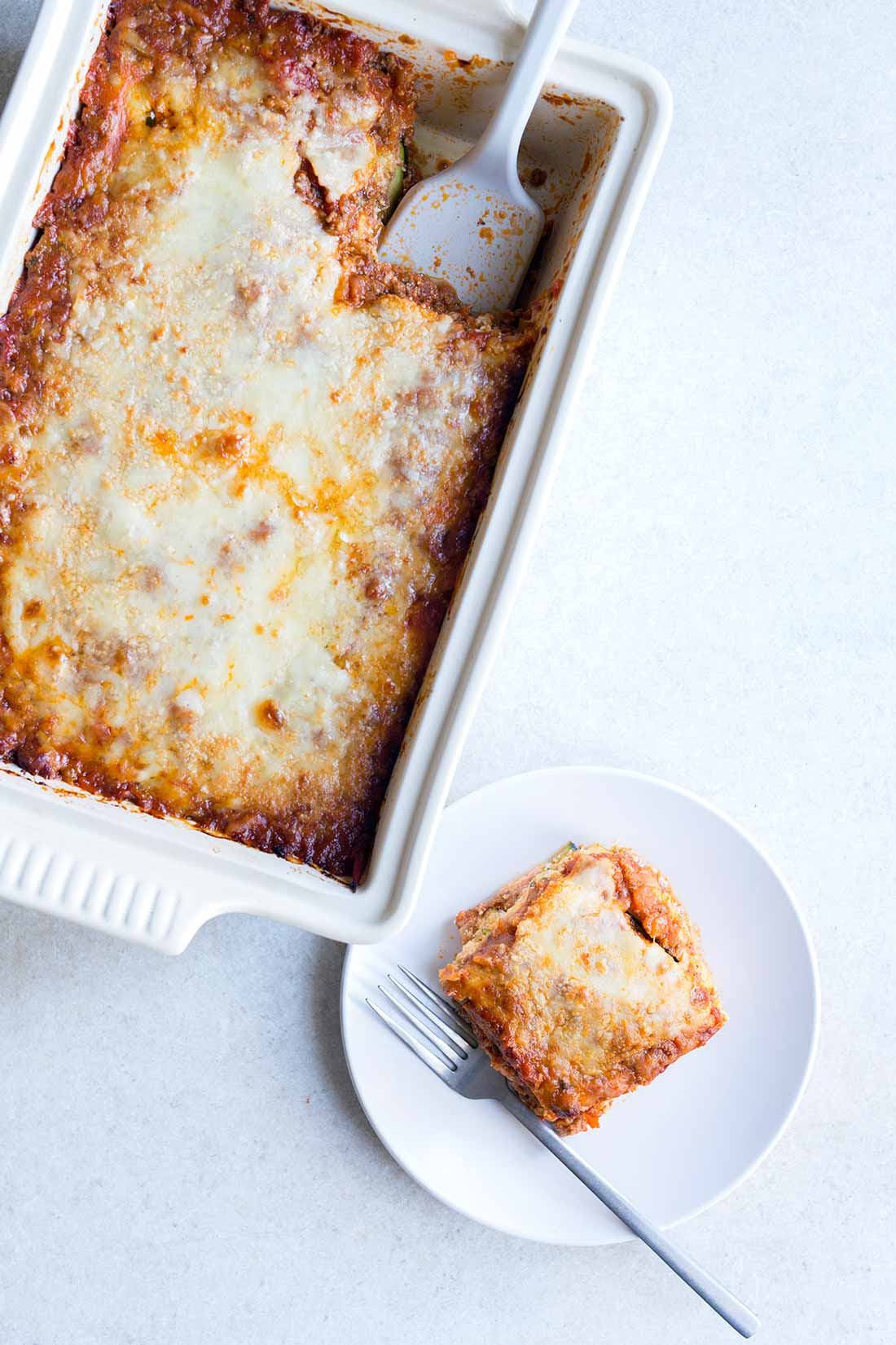 A photo of zucchini lasagna in a casserole dish, next to a slice of lasagna on a plate.