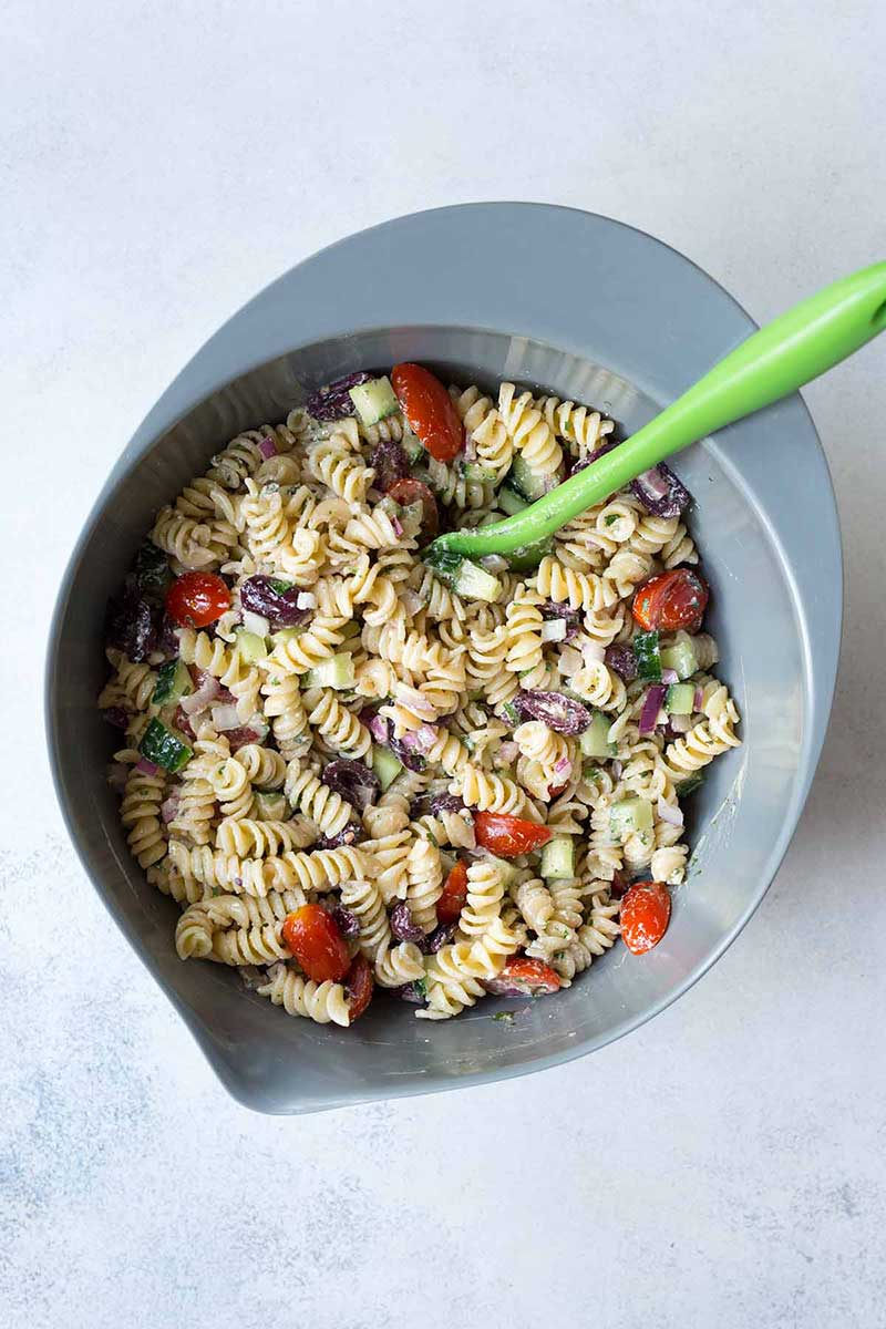 Stirring together greek pasta salad ingredients with a green spatula.