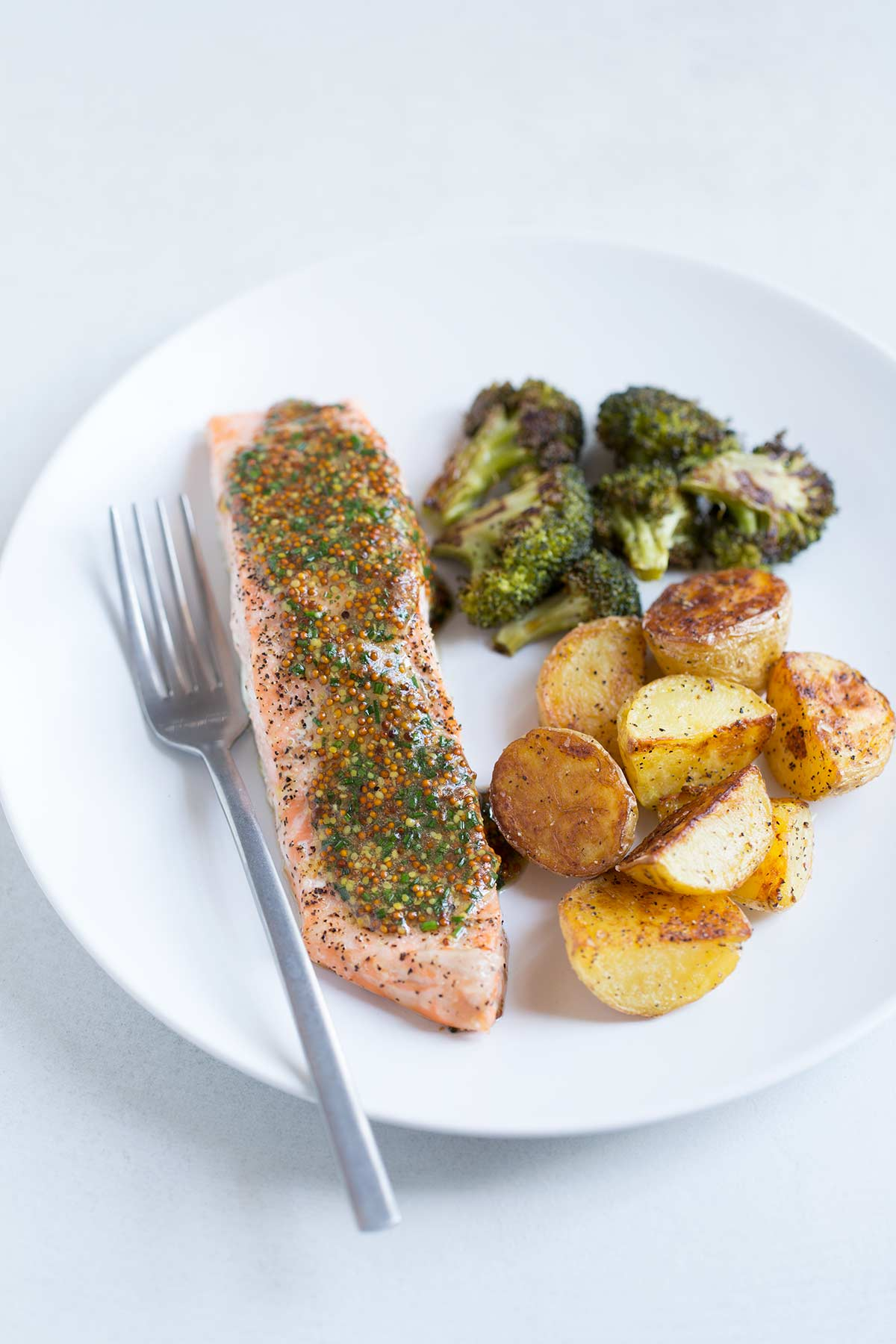 A simple baked salmon recipe topped with a mustard-chive sauce, paired with roasted potatoes and roasted broccoli.