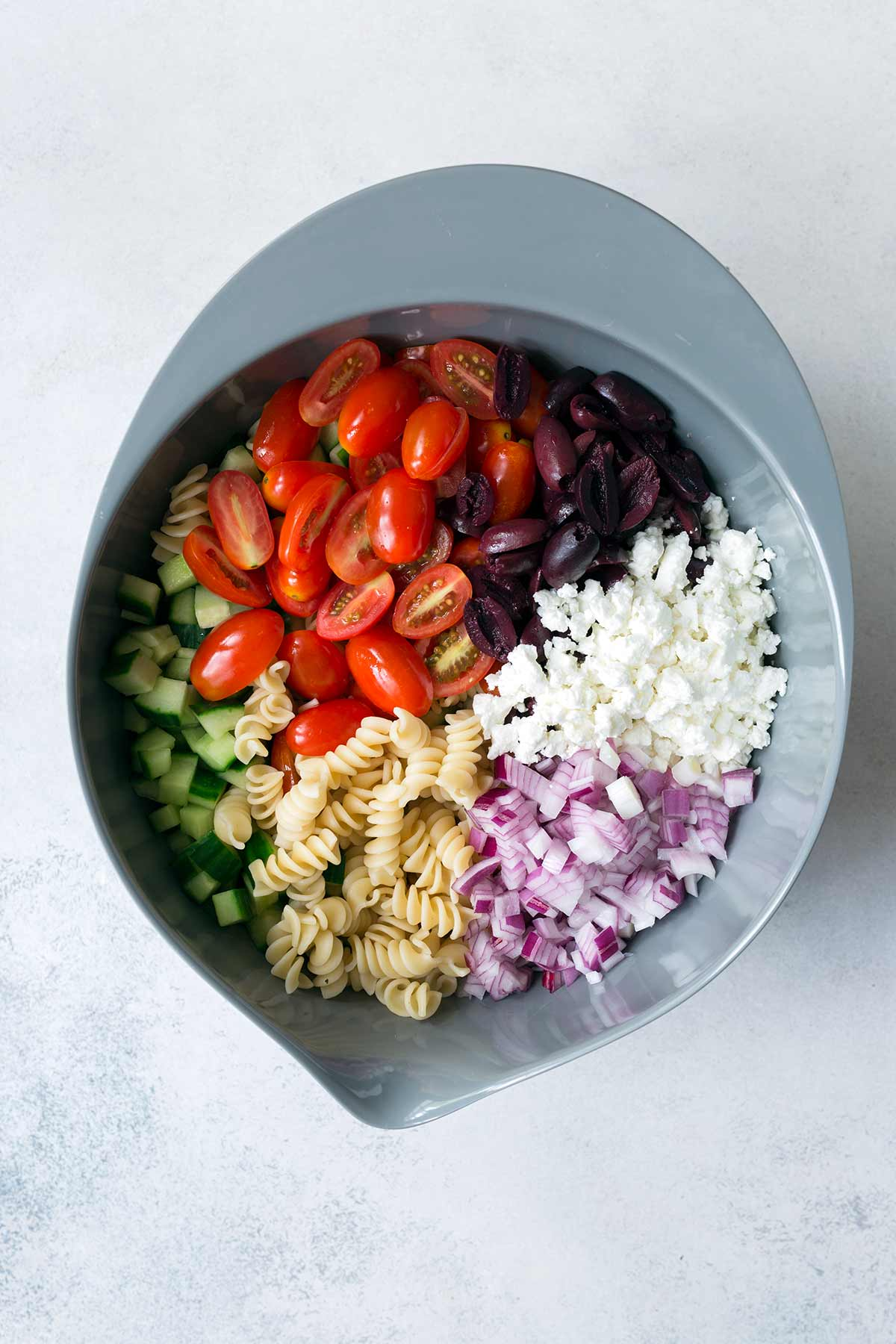 Easy pasta salad recipe ingredients in a mixing bowl.