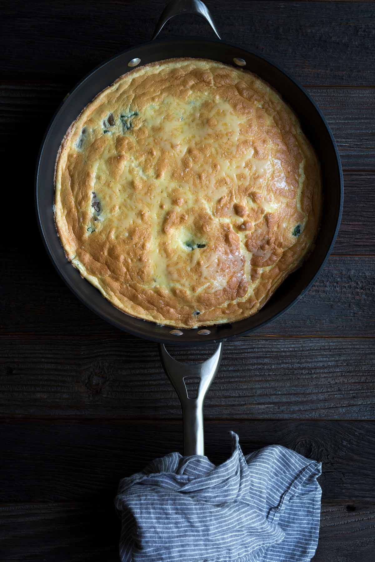 A Swiss, Mushroom and Spinach Frittata in a nonstick skillet.