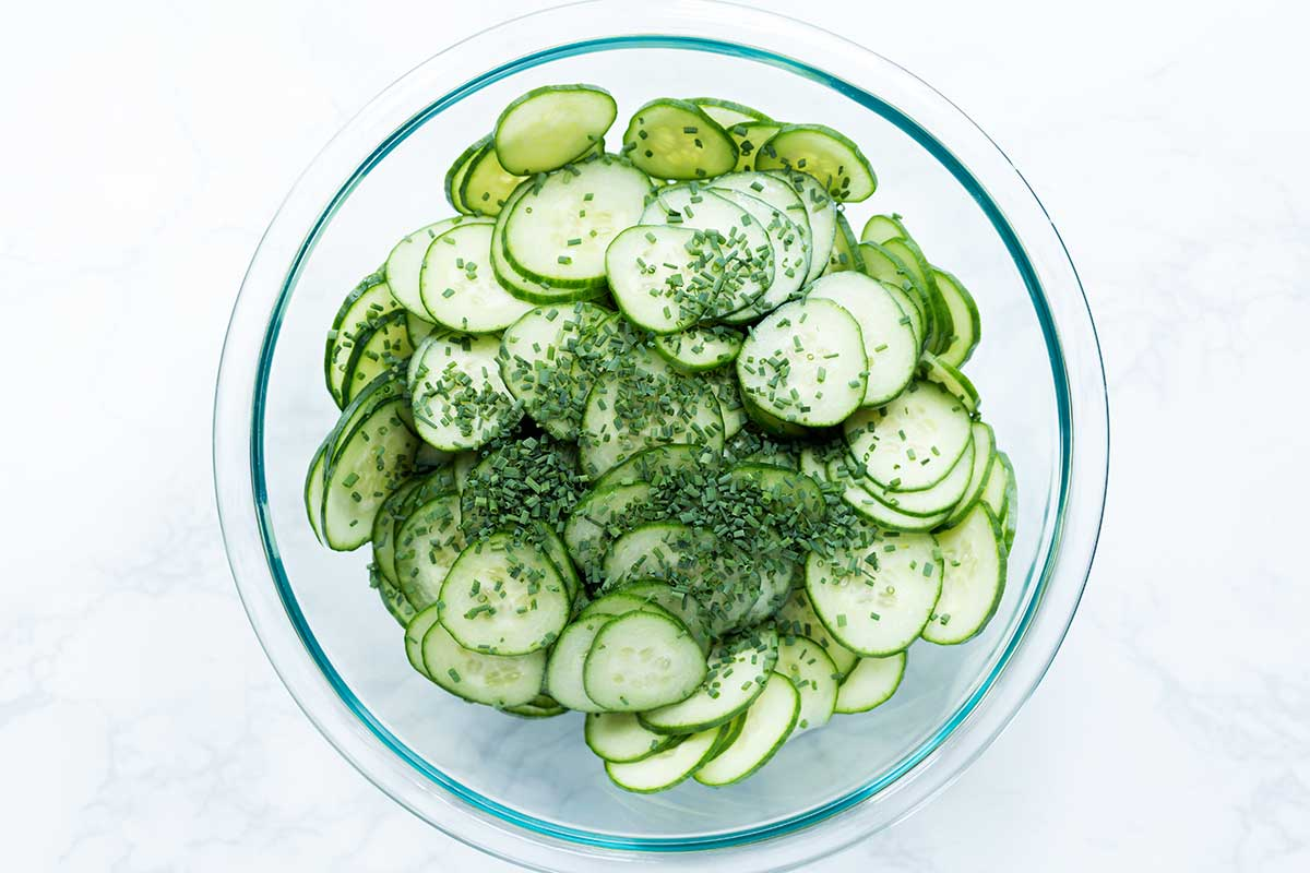 Thinly sliced cucumbers and chopped chives in a large pyrex bowl.