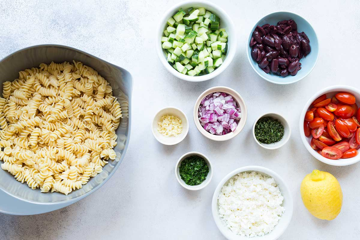 Greek pasta salad ingredients, including cooked pasta, cucumbers, olives, tomatoes, red onions, garlic, and feta cheese.