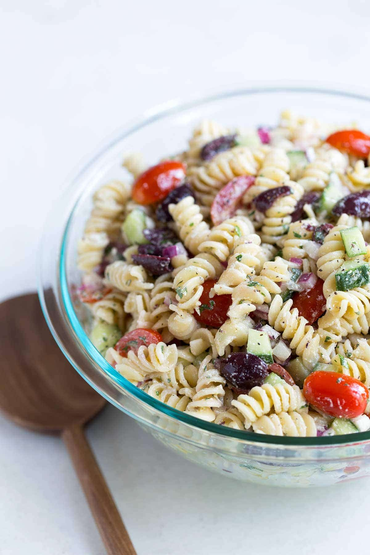 A close up shot of Greek pasta salad in a bowl, next to a wood spoon.