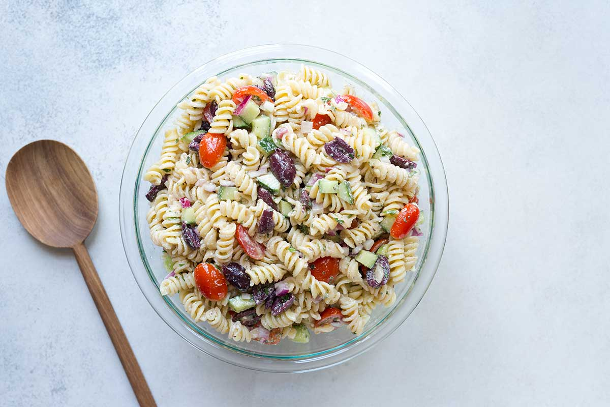 Summer pasta salad in a bowl on a pale backdrop next to a wood spoon.