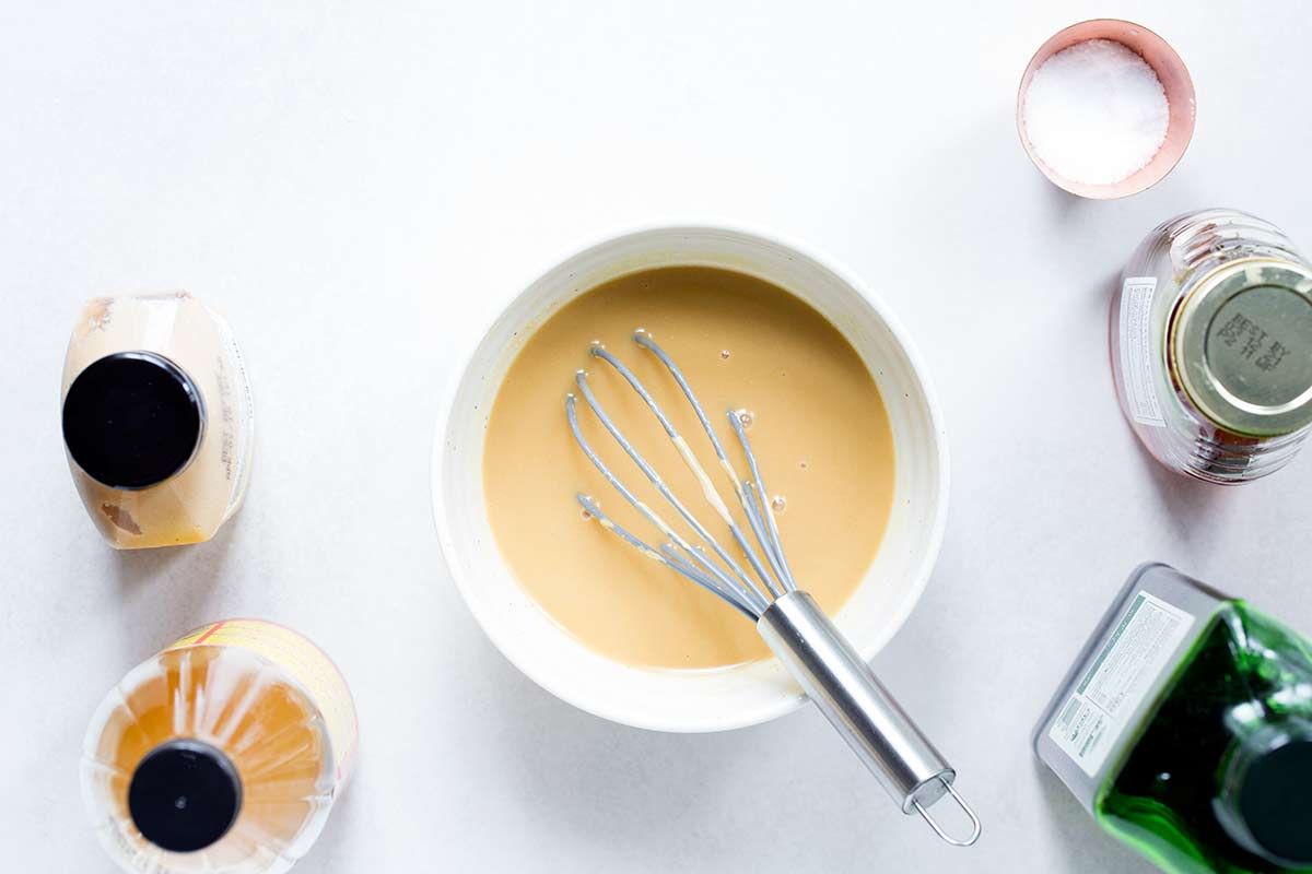 Honey mustard dressing in a bowl with a whisk.