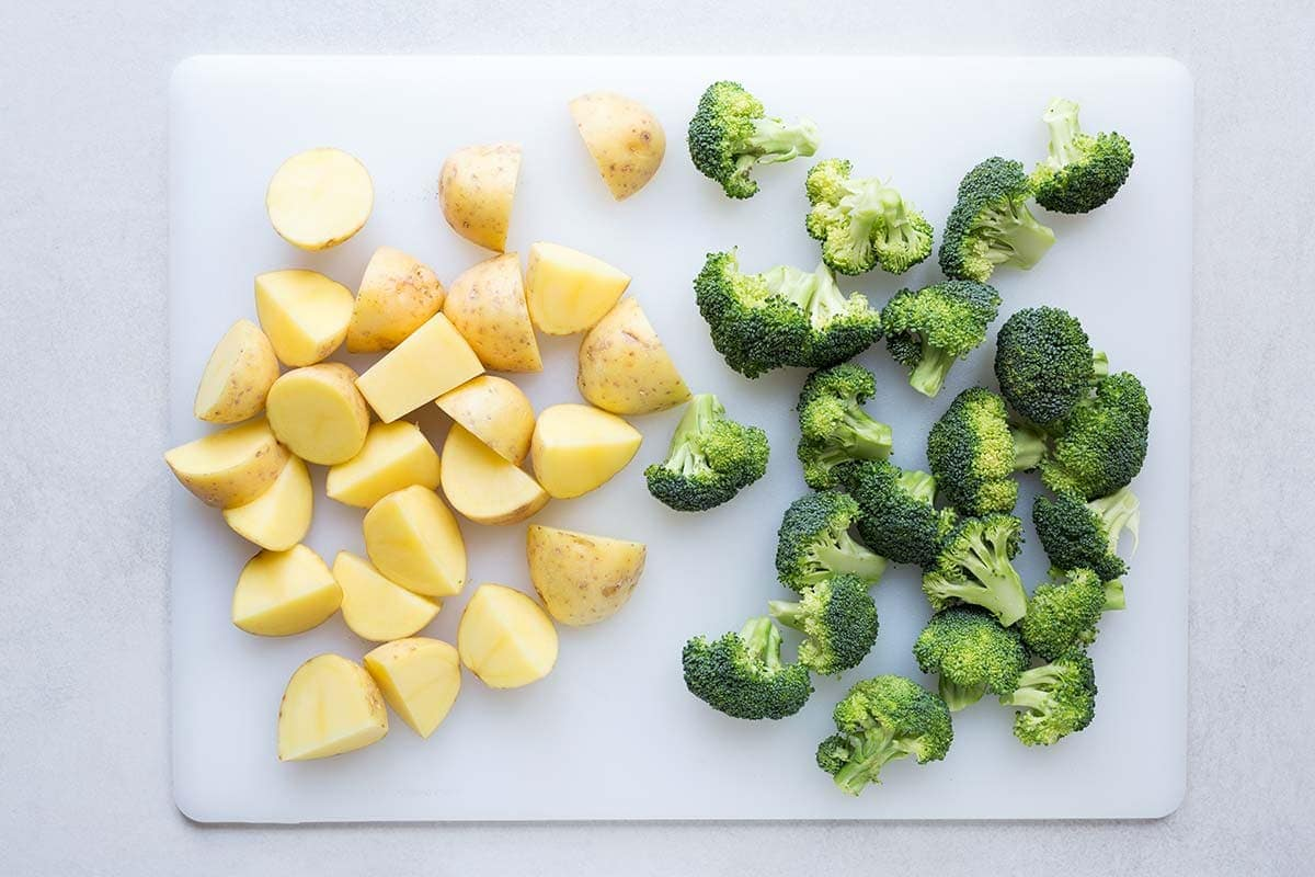 Yukon gold potatoes and broccoli florets cut to similar sizes, displayed on a cutting board.
