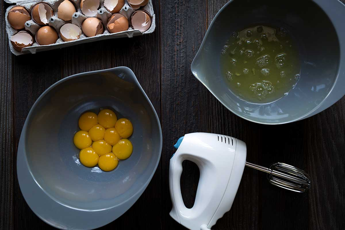 Egg whites and egg yolks separates into separate bowls, next to an electric hand mixer.