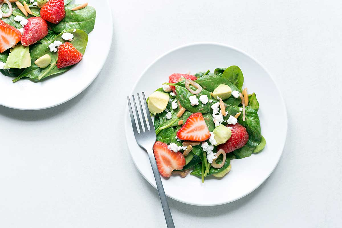 Photo of two spinach salads topped with strawberries, avocados, feta, almonds, and shallots. Shot on a white backdrop.