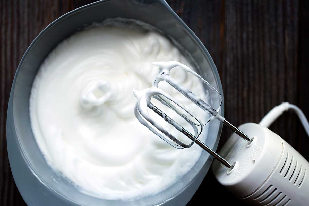 Egg whites that have been whipped to a stiff peak using an electric hand mixer.