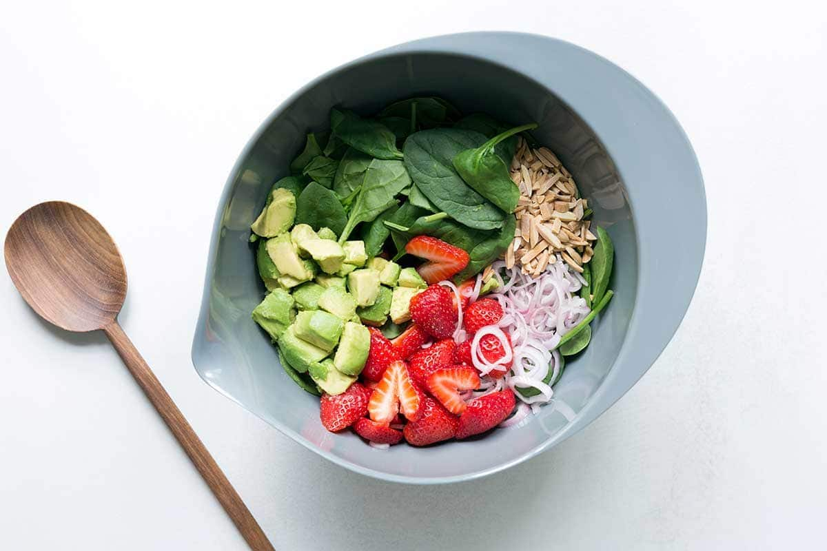A grey bowl filled with ingredients for spinach strawberry salad, next to a wood spoon.