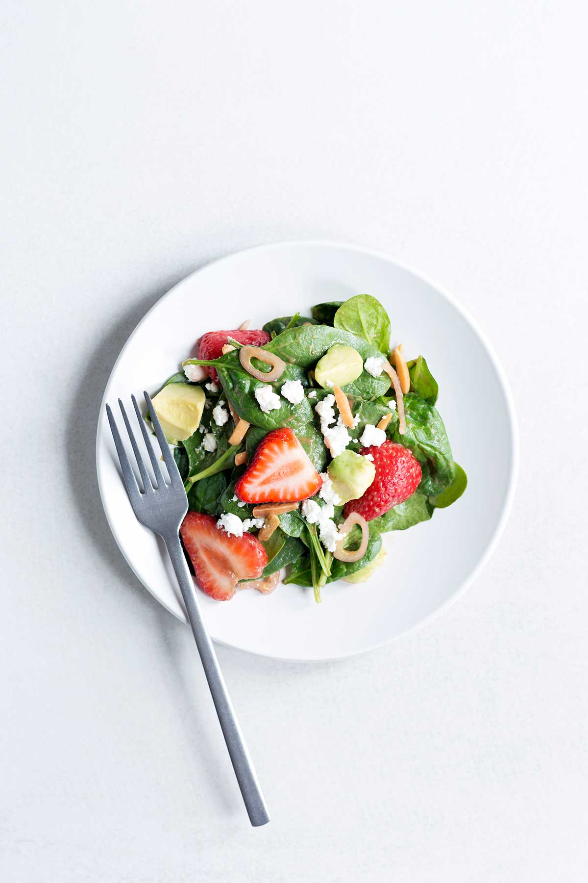 Overhead photo of a strawberry spinach salad on a white plate with a silver fork.
