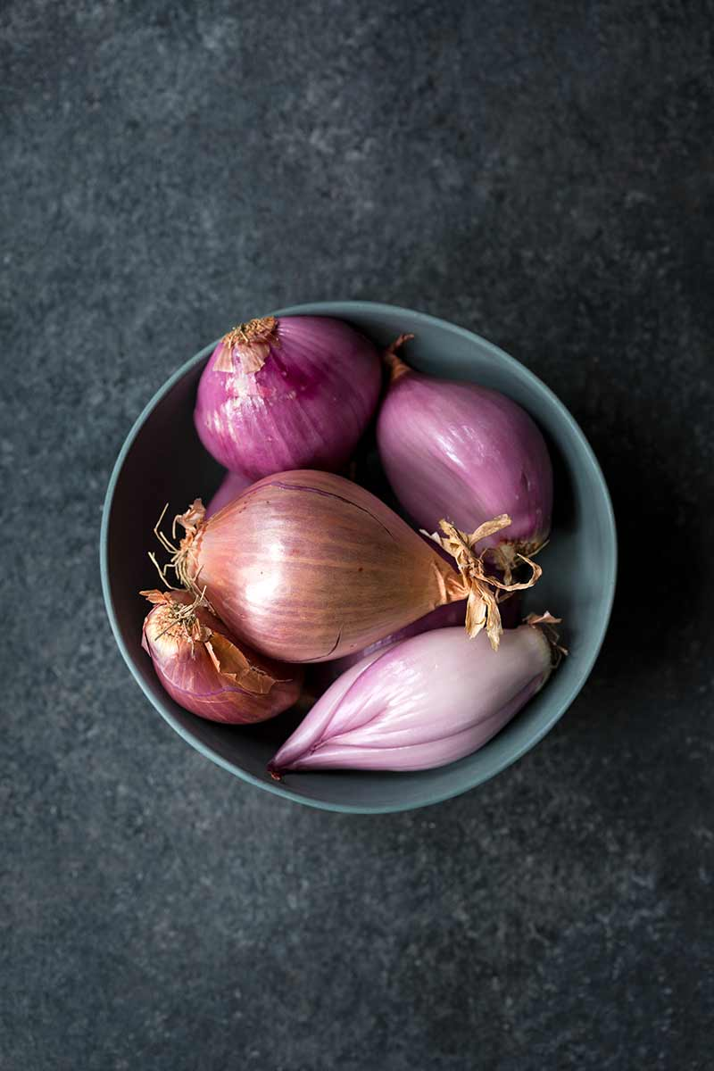 Shallots of various shapes and sizes in a bowl.