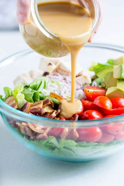Honey Mustard Vinaigrette being poured over salad.