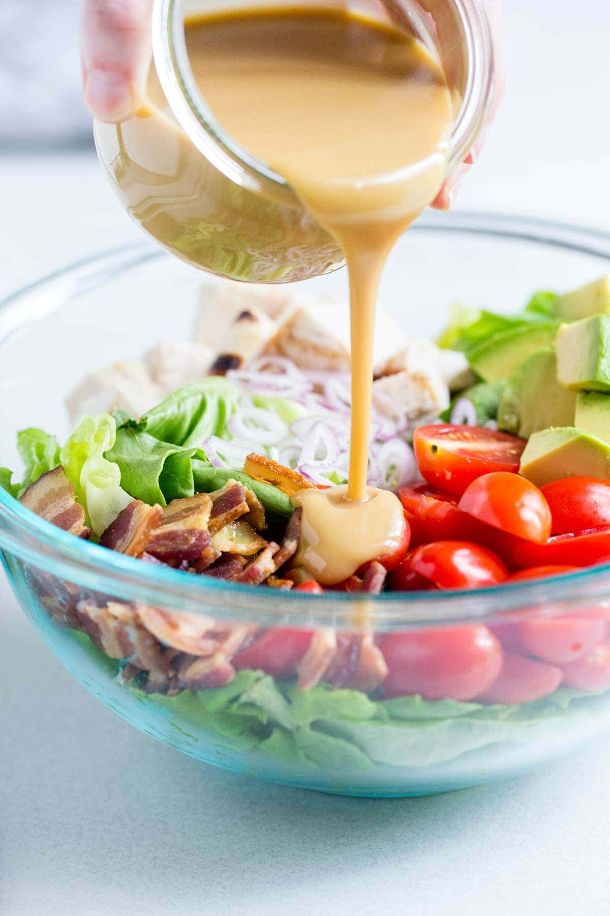 Honey mustard dressing being poured over a large salad.