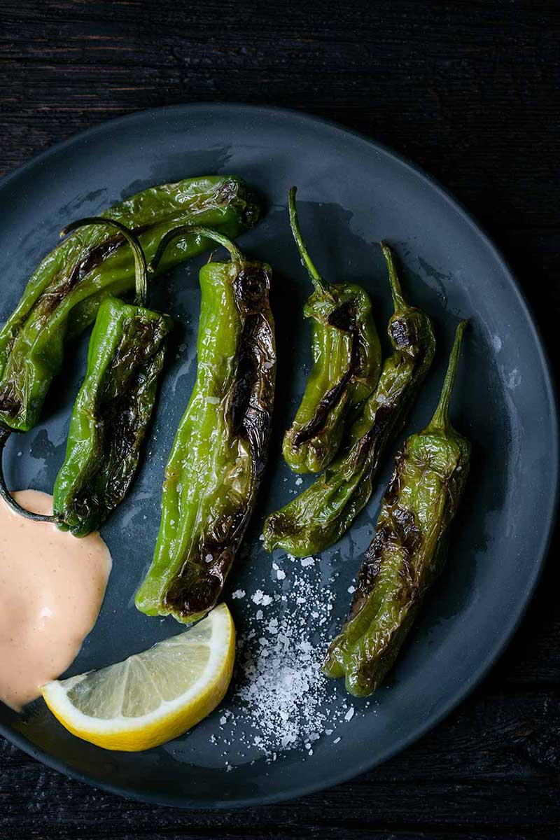 Blistered Shishito Peppers on a plate with coarse salt and sriracha aioli