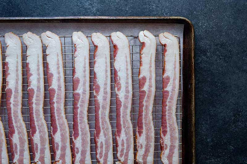 Raw bacon lined up on a sheet pan.
