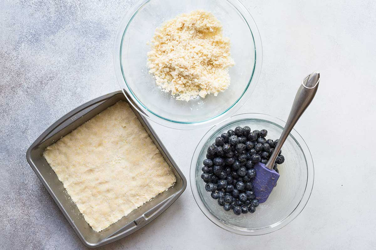 Ingredients to layer blueberry crumb bars, including blueberries and topping.