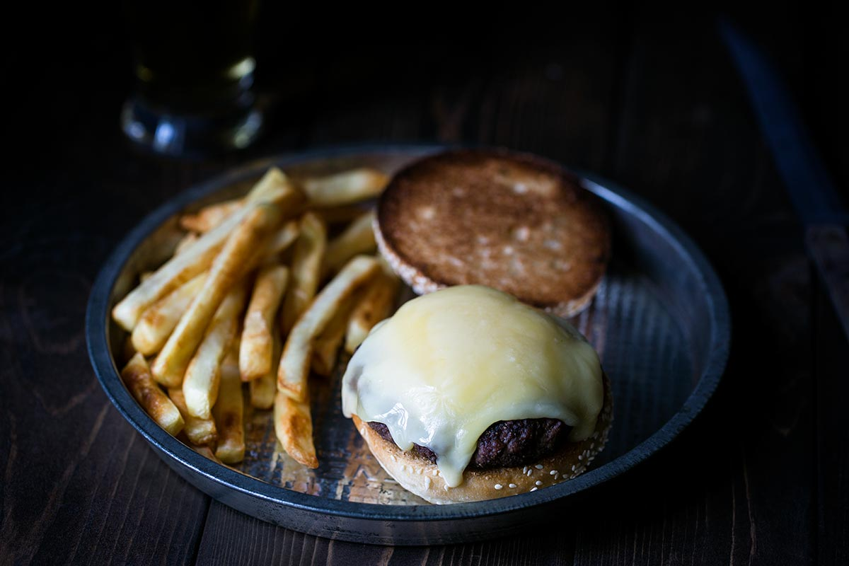 A closeup shot of hot raclette cheese on a grilled burger.